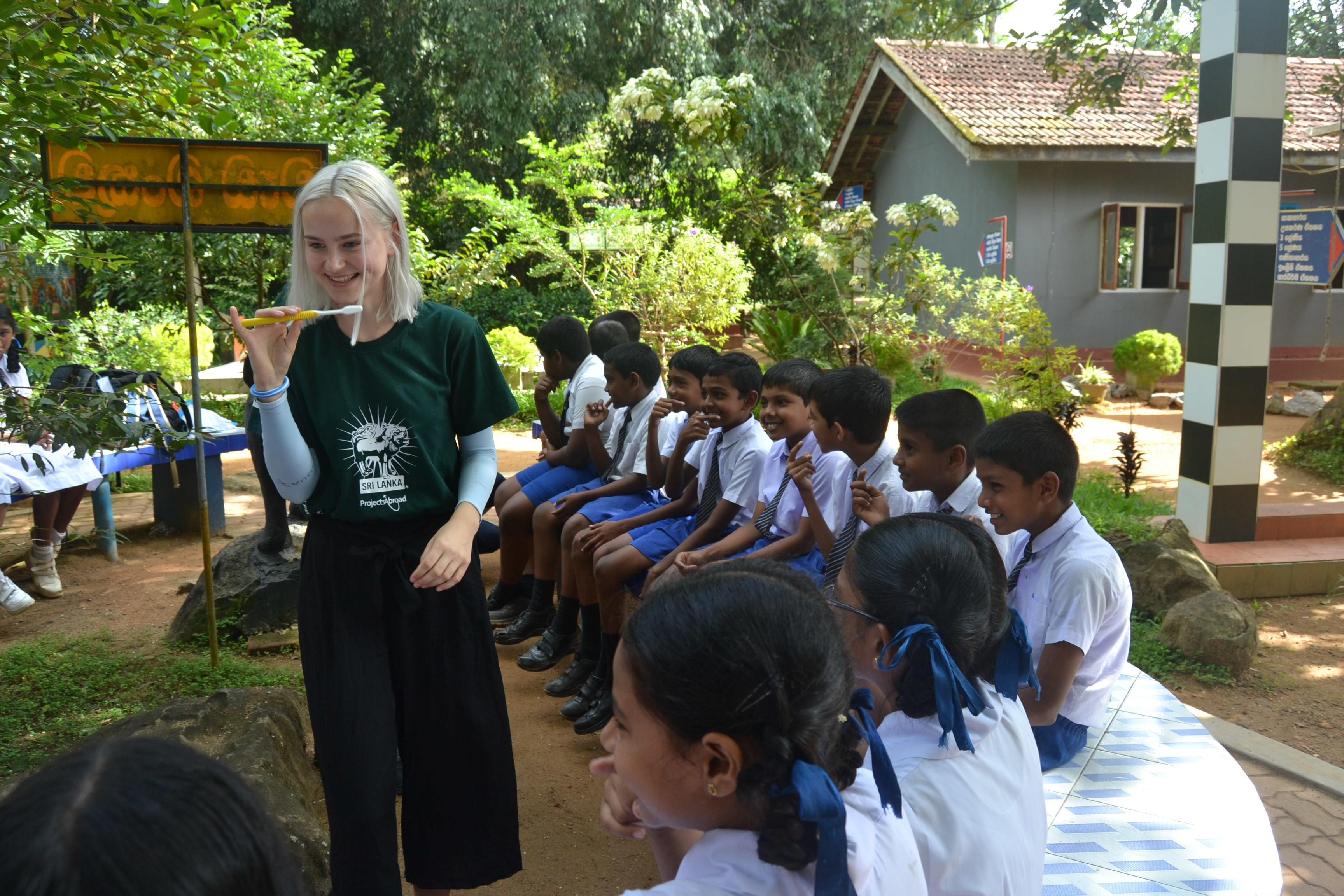 Female Projects Abroad intern can be seen teaching a group of children how to correctly brush their teeth whilst on her public health internship in Sri Lanka.
